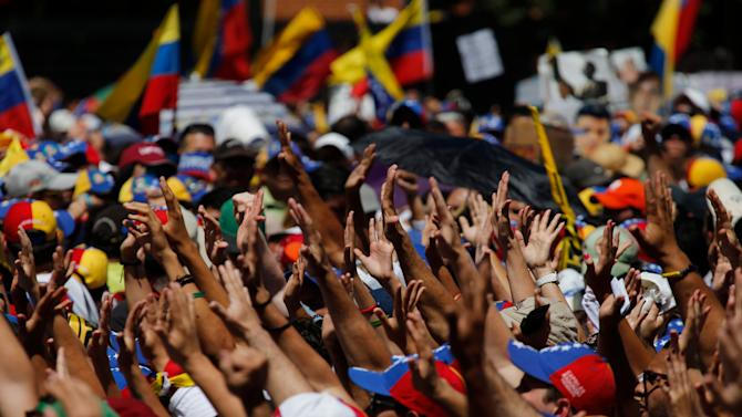 Supporters hold out their hands to greet Carlos Vecchio, the national political coordinator of the Popular Will party, an anti-government group formed by jailed opposition leader Leopoldo Lopez before his arrest, during an anti-government protest in Caracas, Venezuela, Saturday, March 22, 2014. Vecchio addressed the crowd in defiance of an arrest order. Two more people were reported dead in Venezuela as a result of anti-government protests even as supporters and opponents of President Nicolas Maduro took to the streets on Saturday in new shows of force. (AP Photo/Fernando Llano)