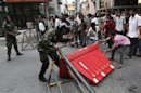 A soldier tries to stop a supporter of former Maldives President Nasheed from removing barricades during a protest in Male