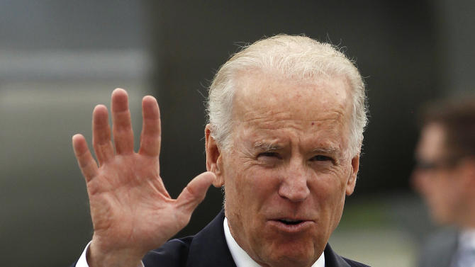 U.S. Vice President Joe Biden waves to reporters after his arrival to a military airport in Bogota, Colombia, Sunday, May 26, 2013. Biden arrived in Colombia as the first stop of a tour that also includes Brazil and Trinidad and Tobago. (AP Photo/Fernando Vergara)