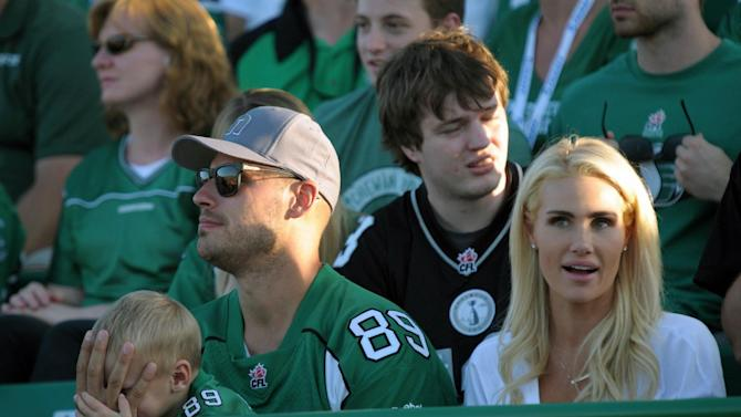 Anaheim Ducks' Ryan Getzlaf and his family watch a CFL football game between the Hamilton Tiger-Cats and the Saskatchewan Roughriders in Regina, Saskatchewan, Sunday, July 26, 2015. (Mark Taylor/The Canadian Press via AP)