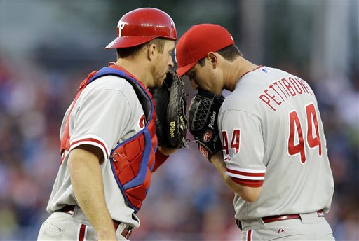 Philadelphia Phillies catcher Erik Kratz, left, talks with starting pitcher Jonathan Pettibone (44) during the third inning of a baseball game against the Washington Nationals at Nationals Park, Satur