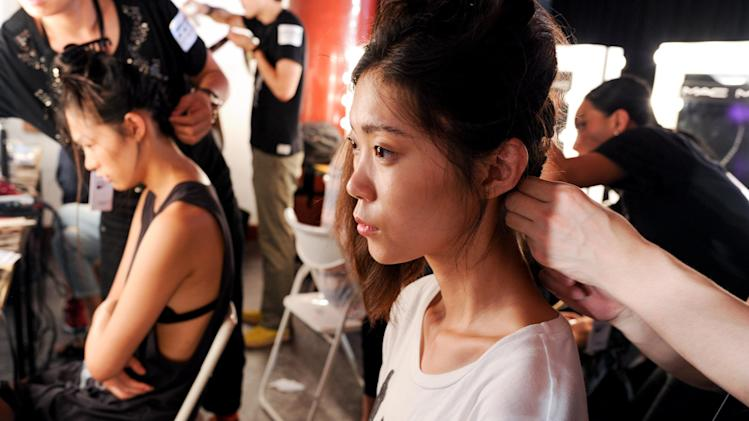 This June 2013 photo released by the Council of Fashion Designers of America (CFDA) shows models being prepared for a fashion show by New York-based designers in Beijing, China. Rag & Bone, Marchesa and Proenza Schouler, among the top in their class of cool, youngish New York-based fashion houses, took a field trip to China recently to introduce themselves to Chinese consumers and to bring home a better understanding of their needs. (AP Photo/Council of Fashion Designers of America, Neil Rasmus)