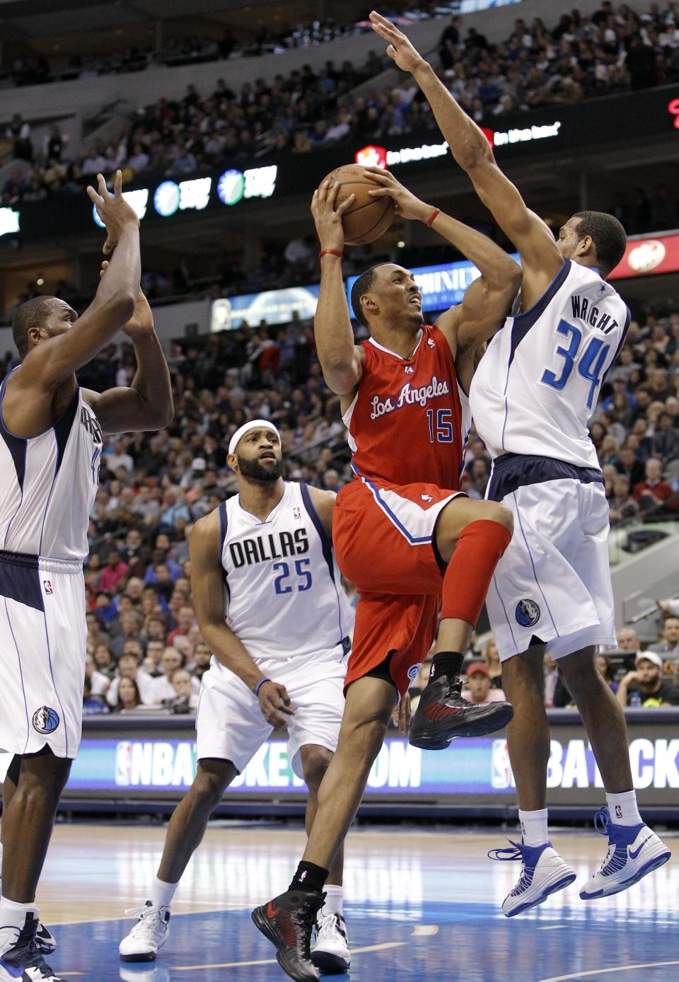 Los Angeles Clippers forward Ryan Hollins (15) looks for room against Dallas Mavericks forwards Brandan Wright (34) and Elton Brand, left,and guard Vince Carter (25) during the first half of an NBA basketball game, Tuesday, March 26, 2013, in Dallas. (AP Photo/Brandon Wade)