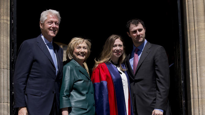 Former U.S. President Bill Clinton, left, and his wife former Secretary of State Hillary Rodham Clinton, second left, pose for photographers with their daughter Chelsea, second right, and her husband Marc Mezvinsky, after they all attended Chelsea's Oxford University graduation ceremony at the Sheldonian Theatre in Oxford, England, Saturday, May 10, 2014. Chelsea Clinton received her doctorate degree in international relations on Saturday from the prestigious British university. Her father was a Rhodes scholar at Oxford from 1968 to 1970. The graduation ceremony comes as her mother is considering a potential 2016 presidential campaign. (AP Photo/Matt Dunham)