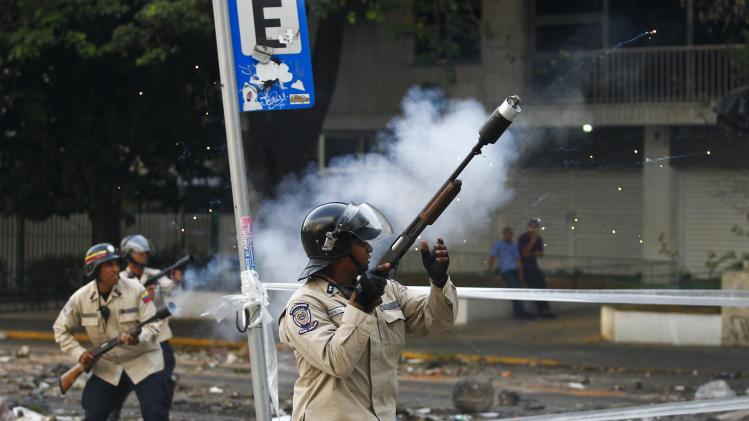 Riot policemen shoot tear gas at anti-government protesters during a protest in Caracas