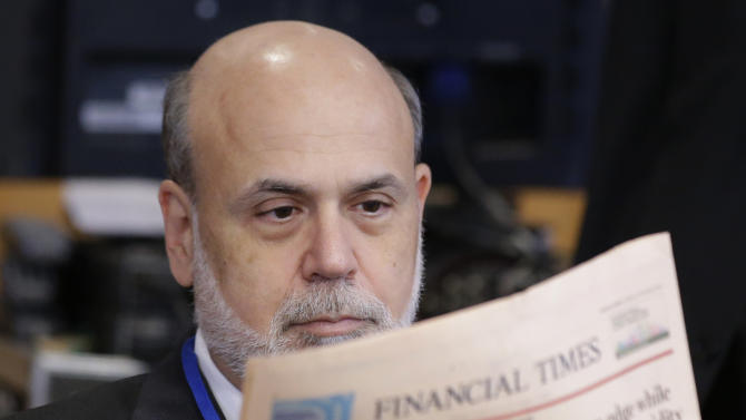 Ben Bernanke, chairman of the Federal Reserve, reads a newspaper before a meeting of the IMFC, during the World Bank/IMF Annual Meetings at IMF headquarters, Saturday, Oct. 12, 2013, in Washington. World finance officials prepared to wrap up three days of meetings in Washington, where fretting about the risk of an unprecedented U.S. debt default overshadowed myriad worries about a shaky global economic recovery. (AP Photo/Alex Brandon)