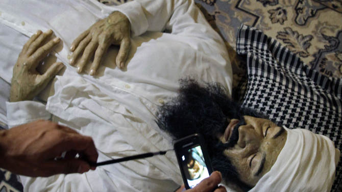 """A student makes a picture with a smart phone of the realistic sculpture of the late al-Qaeda leader Osama bin Laden by artists Alberto Lorente, Manolo Castro and Julio Lorente titled """"He"""" that is on display at the Superior Institute of Arts during the 11th Havana Biennial contemporary art exhibition in Havana, Cuba, Thursday, May 10, 2012. (AP Photo/Javier Galeano)"""