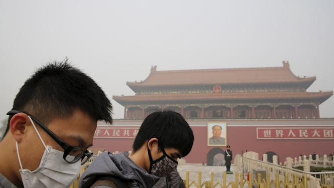 People wearing masks walk past the giant portrait of late Chinese Chairman Mao Zedong, at the Tiananmen Gate during a heavily polluted day in Beijing