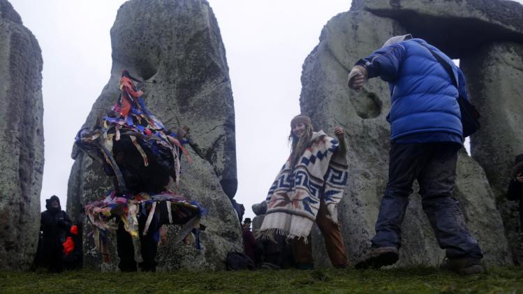 Revellers dance as they celebrate the winter solstice at Stonehenge in Amesbury, southern England