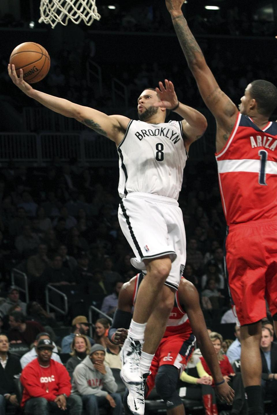 Brooklyn Nets' Deron Williams  (8) goes up against Washington Wizards' Trevor Ariza during the first half of NBA basketball game, Friday, March 8, 2013, in New York. (AP Photo/Mary Altaffer)