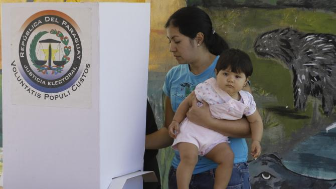 A woman casts her ballot while holding his daughter during general elections in Asuncion, Paraguay, Sunday, April 21, 2013. The elections are an important milestone in Paraguay's attempt to regain the international acceptance it lost when neighboring nations objected to the fast-track removal of President Fernando Lugo.. (AP Photo/Cesar Olmedo)