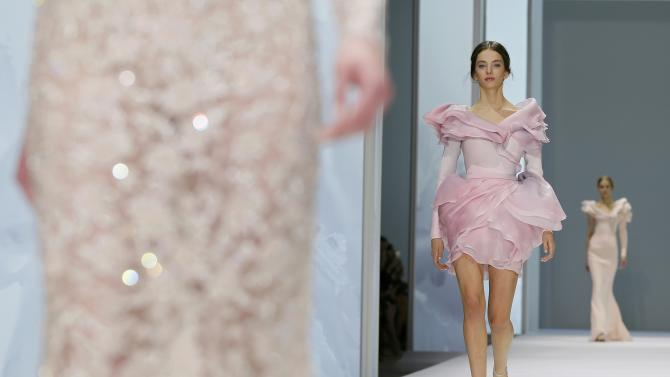 Models present creations by Australian designers Tamara Ralph and Michael Russo as part of their Haute Couture Spring Summer 2015 fashion show for British fashion house Ralph & Russo in Paris