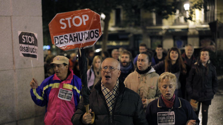 "People hold banners that read: ""Stop Evictions"", during a march against evictions, in Madrid, Friday, Nov. 9, 2012. Officials say a woman fell to her death as bailiffs approached to evict her for non-payment of the mortgage from her fourth-floor apartment in a suburb of the northern Spanish city of Bilbao. Amaia Egana, 53-year-old, who worked at a local bus depot, was married to a former town councilor and had a 21-year-old daughter, launched herself off her balcony Friday, the regional Interior Ministry said. (AP Photo/Andres Kudacki)"
