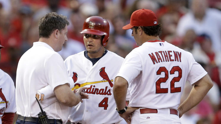 St. Louis Cardinals' Yadier Molina, center, is checked on by manager Mike Matheny, right, and trainer Chris Conroy after injuring his hand while sliding into third during the second inning of a baseball game against the Pittsburgh Pirates Wednesday, July 9, 2014, in St. Louis. St. Louis Cardinals All-Star catcher Yadier Molina will undergo surgery Friday to repair a torn ligament in his right thumb and the team estimated Molina could be sidelined eight to 12 weeks