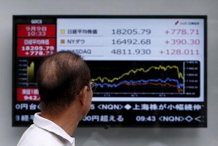 A pedestrian looks at an electronic board showing the graph of the recent fluctuations of market indices of ,Japan's Nikkei average, Dow Jones and NASDAQ outside a brokerage in Tokyo