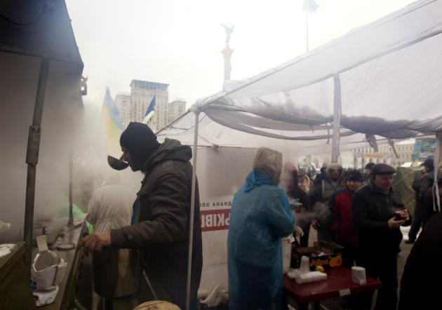 Pro-European integration protestors make food and tea at a field kitchen at Independence square in Kiev