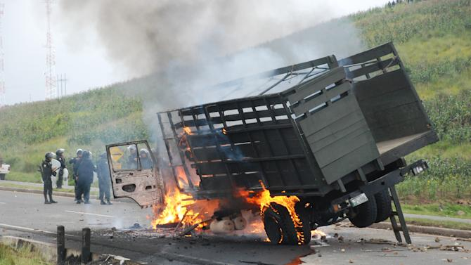 National Civil Police agents stand next to a burning army truck during clashes with peasants protesting against the cost of electricity in Santa Catarina Ixtahuacan, west of Guatemala City on Thursday Oct. 4, 2012. At least two people have been killed and dozen others seriously wounded in the confrontation between protesters and security forces. (AP Photo)