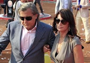 Gymnast Comaneci and former tennis player Nastase of Romania leave the court after the awards ceremony at the Romanian Open tennis tournament in Bucharest