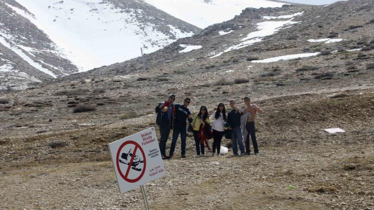 People pose for a photograph on a mountain without snow, in north of Beirut