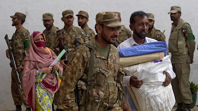 A Pakistani army soldier, escorts election staff carrying ballots for tomorrow's elections, in Islamabad, Pakistan, Friday, May 10, 2013. An especially violent spate of killings, kidnappings and bombings marred the run-up to Pakistan's nationwide election, capped Thursday by the abduction of the son of a former prime minister as he was rallying supporters on the last day of campaigning before the historic vote. (AP Photo/B.K. Bangash)