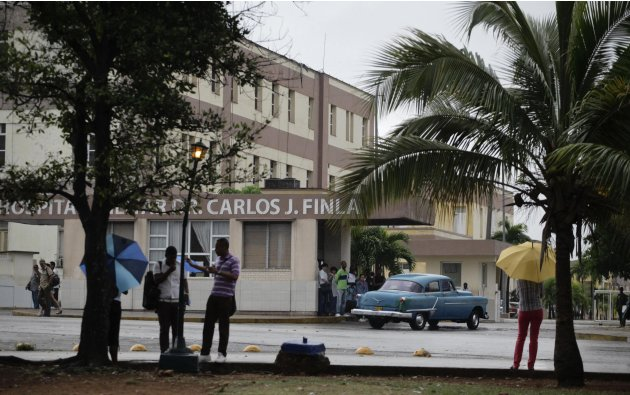 People stand near the Carlos J. Finlay Military Hospital where U.S. government contract worker Alan Gross is held prisoner in Havana