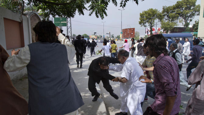 A supporter, center in white dress, of Pakistan's former President and military ruler Pervez Musharraf scuffles with lawyer outside an anti-terrorism court, where Musharraf appeared in Rawalpindi, Pakistan, Tuesday, April 23, 2013. Musharraf appeared before anti-terrorism court over the assassination of former prime minister Benazir Bhutto's case, official said.  (AP Photo/Anjum Naveed)