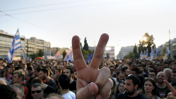 A protester flashes a victory sign during an anti-austerity demonstration in Syntagma Square in Athens