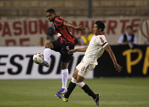 David of Brazil's Atletico Paranaense, left, fights for the ball with Christofer Gonzalez of Peru's Universitario during a Copa Libertadores soccer match in Lima, Peru, Thursday, March 13, 201