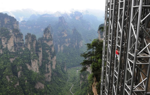 France's daredevil climber Casanova climbs the Bailong Elevator near a cliff in the Wulingyuan tourism area of Zhangjiajie