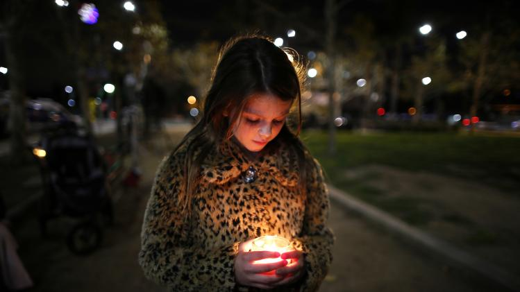 Sophia Anderson, who was born in South Africa, participates in a candlelight vigil in memoriam of Nelson Mandela's death, in Los Angeles