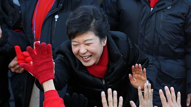 South Korea's presidential candidate Park Geun-hye of ruling Saenuri Party is greedy by supporters during her presidential election campaign in Busan, South Korea, Tuesday, Dec. 18, 2012. South Korea's presidential election is scheduled on Dec. 19. (AP Photo/Yonhap. Lee Ji-eun)  KOREA OUT