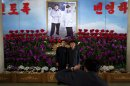 FILE - In this Friday, April 12, 2013 file photo, two men hold hands as they pose for photos in front of a portrait of the late North Korean leader Kim Jong Il, right, and his son Kim Jong Un at a flower show featuring thousands of Kimilsungia flowers, named after the late leader Kim Il Sung, in Pyongyang, North Korea. Enemy capitals, North Korea said, will be turned