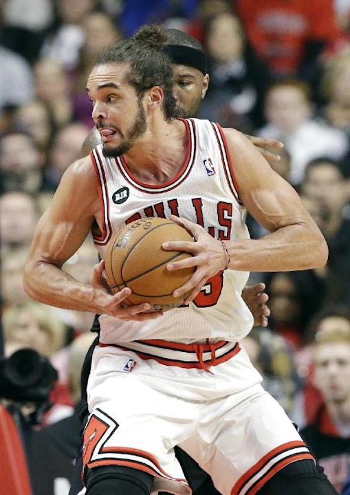 Chicago Bulls center Joakim Noah (13) works with the ball against Sacramento Kings forward Reggie Evans during the first half of an NBA basketball game in Chicago on Saturday, March 15, 2014