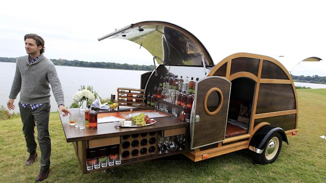 A model displays the Bulleit Frontier Whisky Woody-Tailgate Trailer during the unveiling of the Neiman Marcus 2012 Christmas Book in Dallas, Tuesday, Oct. 9, 2012.  The trailer is priced for sale at $150,000.  (AP Photo/LM Otero)