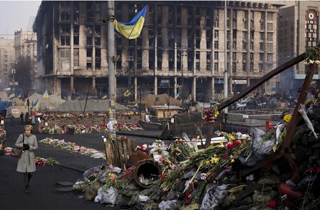 A woman walks past a barricade covered in flowers left to those killed in recent clashes in Kiev's Independence Square, Ukraine, Friday, March 7, 2014. In the background is the Trade Unions Buildi