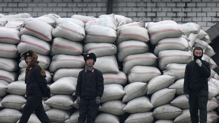 North Koreans stand by sacks of fodder at the banks of the Yalu River near the North Korean town of Sinuiju