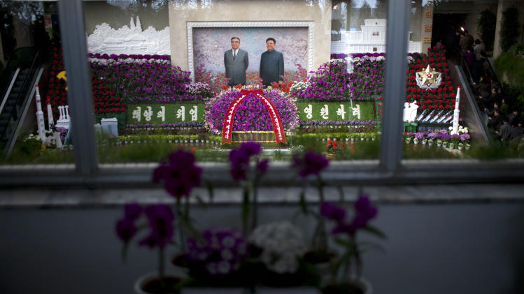 A portrait of North Korea's late leaders, Kim Il Sung, and Kim Jong Il, is displayed at a flower show featuring thousands of Kimilsungia flowers, named after Kim Il Sung, in Pyongyang, North Korea, Friday, April 12, 2013. (AP Photo/Alexander F. Yuan)