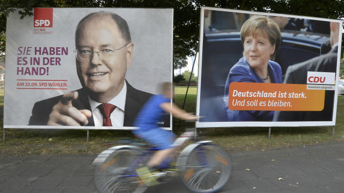 """A man on a bicycle passes election posters, showing the two top candidates for next German chancellor at a street in Duisburg, western Germany, Thursday, Aug. 29, 2013. Peer Steinbrueck of the Social Democratic Party, SPD, left, will challenge German chancellor Angela Merkel of the governing Christian Social Democrats, CDU, right. Germans will vote on Sept. 22, 2013. Slogan on the SPD poster reads """"you have it in your hand"""" and on the CDU poster """"Germany is strong. And should stay that way."""" (AP Photo/Martin Meissner)"""