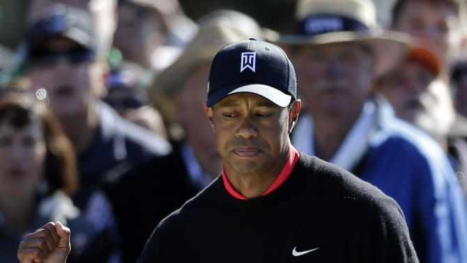 Tiger Woods raises a fist after hitting out of a bunker on the 11th hole during the fourth round of the Farmers Insurance Open golf tournament at the Torrey Pines Golf Course Monday, Jan. 28, 2013, in San Diego. (AP Photo/Gregory Bull)