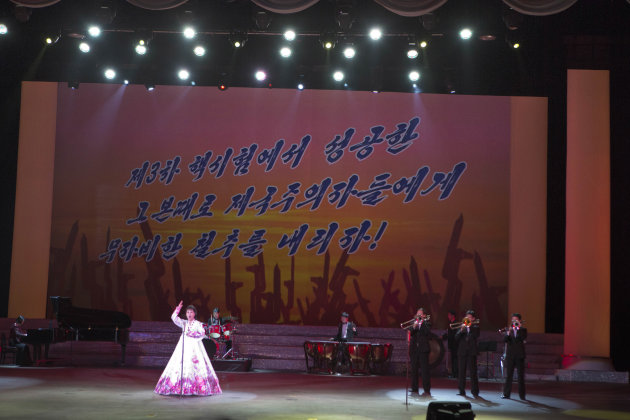 "A North Korean musical performance is held in Pyongyang with  the words ""Let's strike the imperialists mercilessly with the same success we had carrying out the 3rd nuclear test"" projected on a screen"