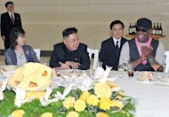 Kim Jong-Un (centre), his wife Ri Sol-Ju and Dennis Rodman at a dinner in Pyongyang last night. The pair were photographed joking together at the post-game reception, where Rodman, sporting a pink neck scarf and with piercings in his nose and lip, appeared to be enjoying a martini