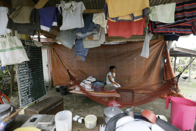 A flash flood survivor makes use of a waiting shed as a temporary shelter after Typhoon Bopha destroyed most of the houses in the area in New Bataan township, Compostela Valley in the southern Philipp