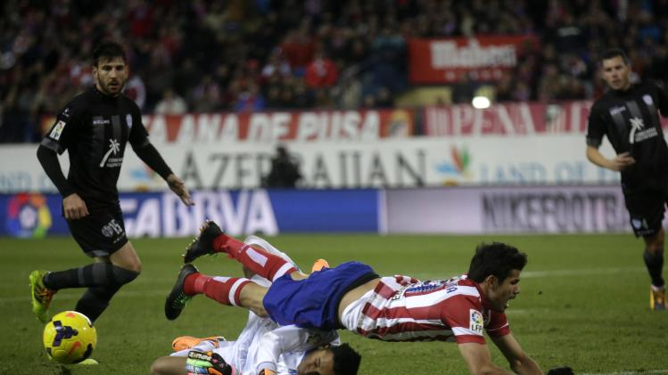 Atletico Madrid's Costa falls over Levante's goalkeeper Navas during their Spanish first division soccer match at Vicente Calderon stadium in Madrid