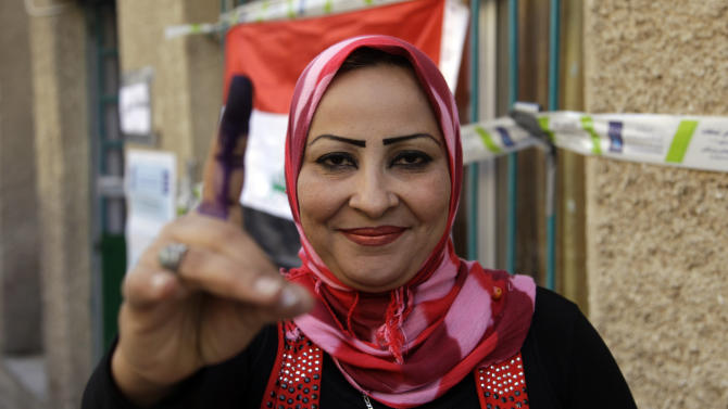 An Iraqi woman displays her ink-stained finger at a polling center during the country's provincial elections in Baghdad, Iraq, Saturday, April 20, 2013.  Polls opened amid tight security in Iraq on Saturday for regional elections in the country's first vote since the U.S. military withdrawal, marking an important test of the country's stability.(AP Photo/ Khalid Mohammed)
