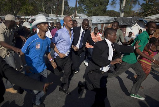 Haiti's President Michel Martelly, third from left, jogs around the University of Haiti protected by bodyguards in Port-au-Prince, Haiti, Friday, Feb. 17, 2012. Witnesses say rocks were thrown at Martelly from behind a university building while he strolled through the capital's downtown area in a Carnival procession.  Martelly was taken without injury to the nearby National Palace, but left it about an hour later and proceeded around the campus. (AP Photo/Ramon Espinosa)