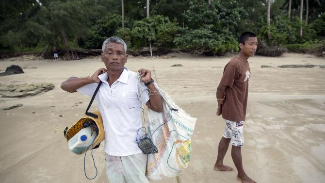 Hong Klathalay carries gear on his way to his fishing boat n Khao Lak
