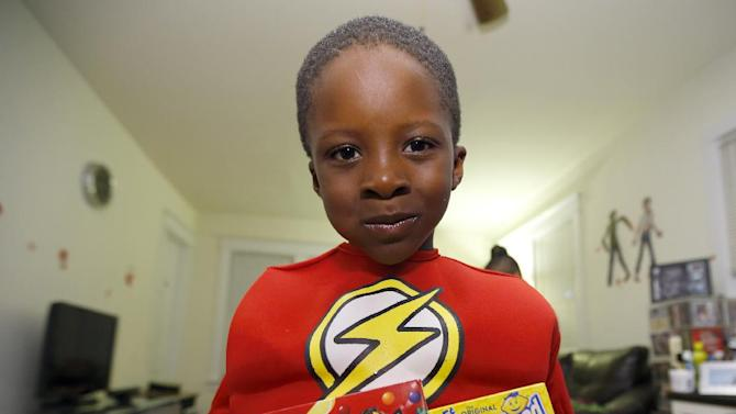 IMAGE DISTRIBUTED FOR FERRARA CANDY COMPANY - Kehinde Iribhogbe, 6, holds boxes of Lemonhead candies in an apartment in Forest Park, Illinois, home to the Ferrara Candy Company factory since 1908, as he and friends celebrated Halloween by honoring the newest traditions, thanks to Lemonhead Candies and #Yelloween, of painting pumpkins yellow Friday, October 31, 2014. Yellow is the new orange this year. (Photo by Jeff Haynes/Invision for Ferrara Candy Company/Lemonhead/AP Images)