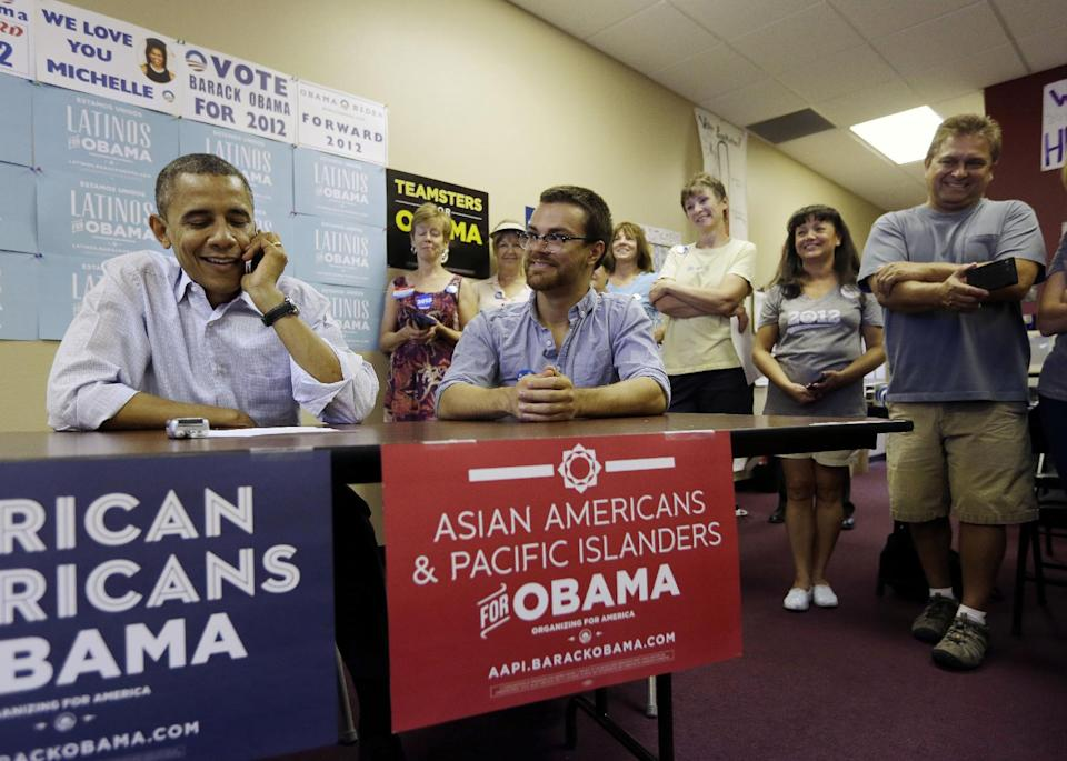 President Barack Obama, left, uses a cell phone to call supporters during a visit to a local campaign office, Monday, Oct. 1, 2012 in Henderson, Nev. Sitting with Obama is Casey Adams, center, Regional Field Director. (AP Photo/Pablo Martinez Monsivais)