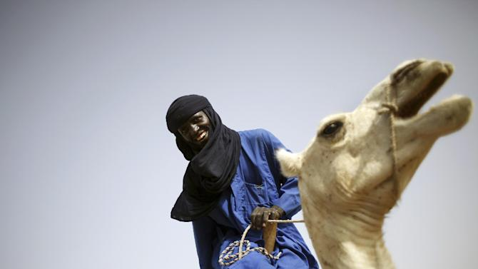 In this picture taken Sunday, July 22, 2012, a Tuareg man smiles as his camel rises from lying down at the livestock market in the desert village of Sakabal, Niger, 220 kms (140 miles) north of Maradi. Eighty percent of Niger's people and 100 percent of the landlocked nation's rural population depend on livestock, including camel, cows, sheep and goats, for some part of their income. For generations, nomads have lived in a precarious equilibrium with the sky above them. When the first rains come, they head north toward the Sahara desert, where the grass is said to be saltier, packed with minerals. They time their movements according to the clouds, waiting for the second major downpour, before making a U-turn to head back to the greener south. If they miscalculate, they can end up stranded. As the grass turns yellow, their animals become too weak to walk. (AP Photo/Jerome Delay)