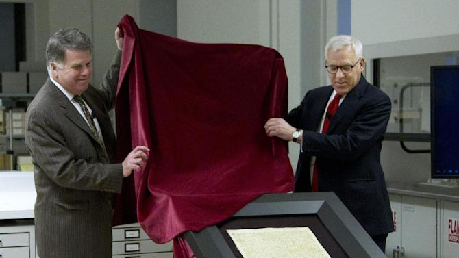 Carlyle Group co-founder and Magna Carta owner David Rubenstein, right, and Archivist of the U.S. David Ferriero, unveil the 1297 Magna Carta in its new state-of-the-art encasement at the National Archives in Washington, Thursday, Feb. 2, 2011.  (AP Photo/Manuel Balce Ceneta)
